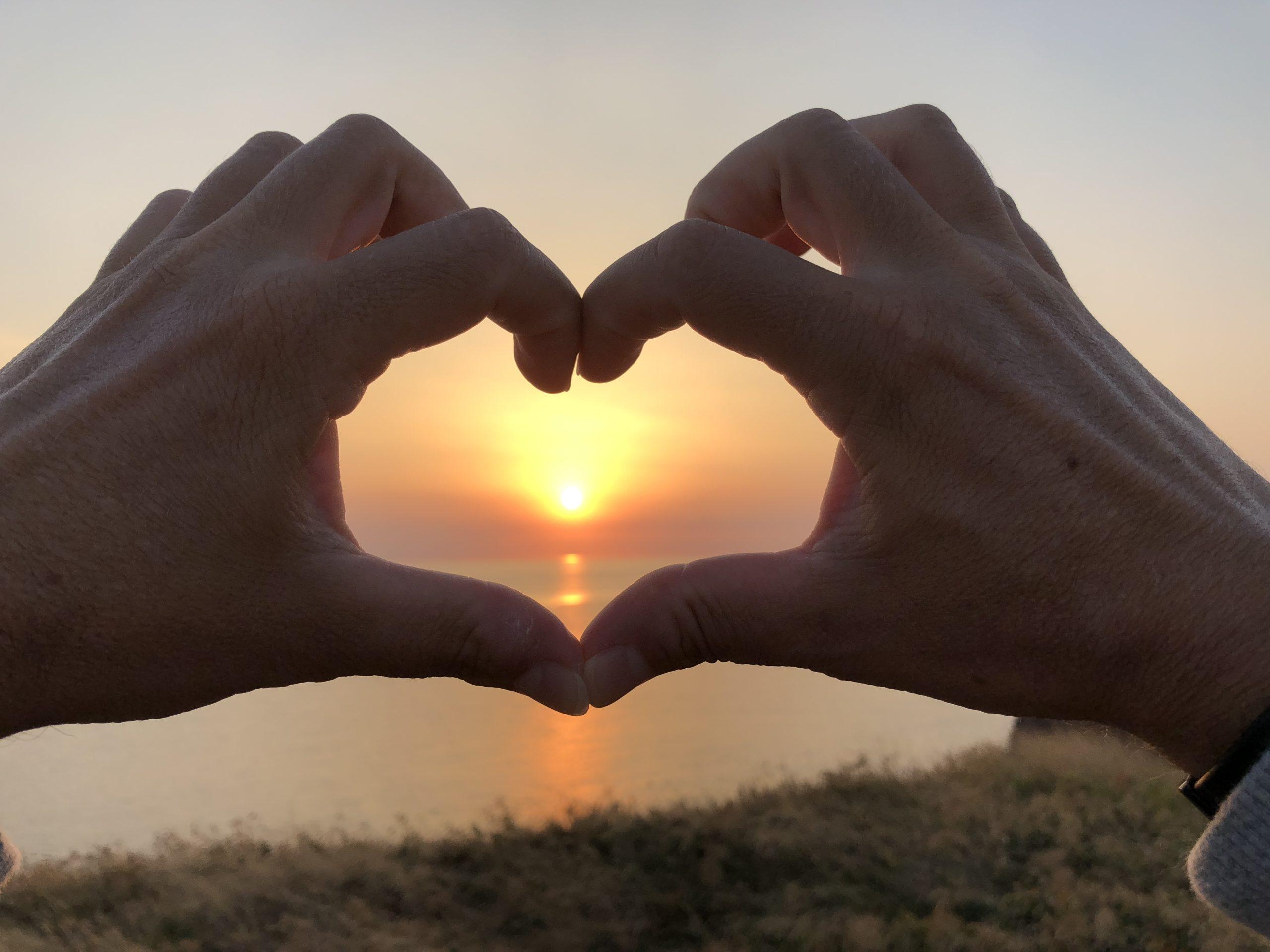 Zwei Hände formen ein Herz, in dessen Mitte die untergehende Sonne zu sehen ist